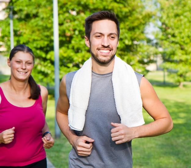 公園を走っている陽気な白人カップルの肖像画