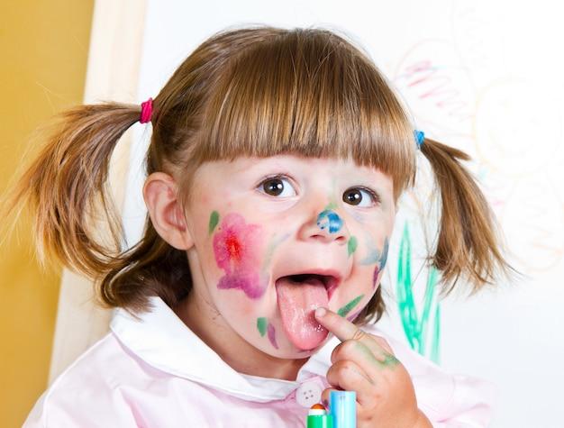 小さな女の子が塗料を描画します
