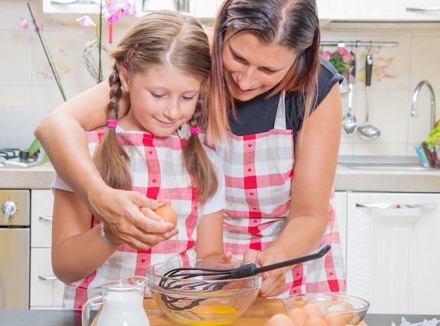 Мать и дочь разбивают яйца, готовя вместе на кухне