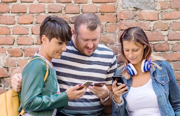 Группа друзей, смотрящих умные мобильные телефоны