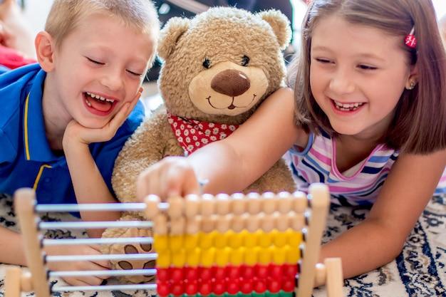 Маленькие дети играют со счетами дома
