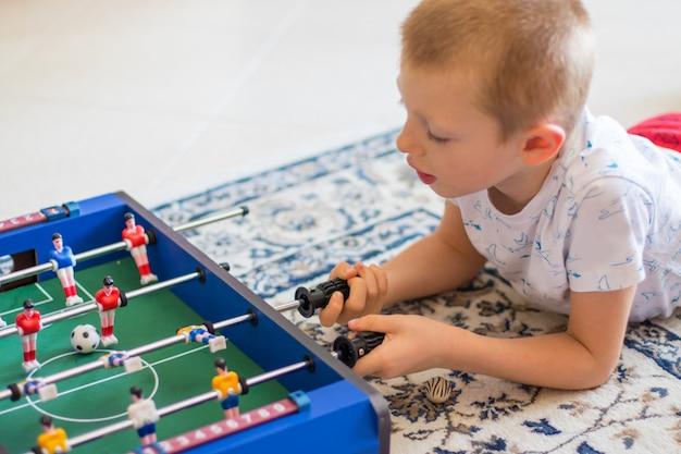 Маленький мальчик играет в настольный футбол