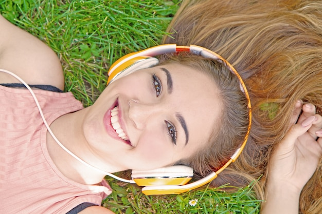 夏の牧草地でヘッドフォンで音楽ストリーミングを聴いている女の子
