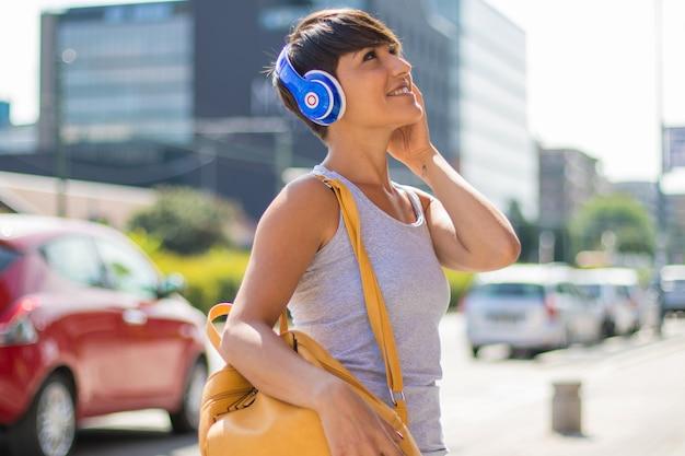 美しい女性はヘッドフォンで音楽を聴いています
