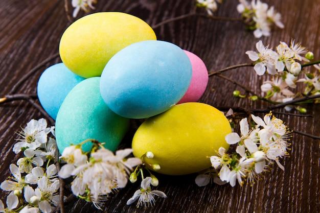 Пасхальные яйца с весенним цветком на деревянном столе