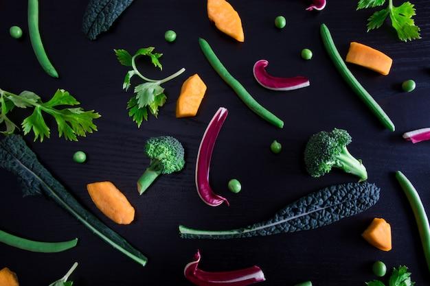 Вид сверху различных и красочных овощей, изолированных на черной поверхности