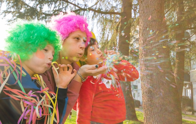 母と彼女の子供たちはカーニバルの衣装で紙吹雪で遊んでいます。