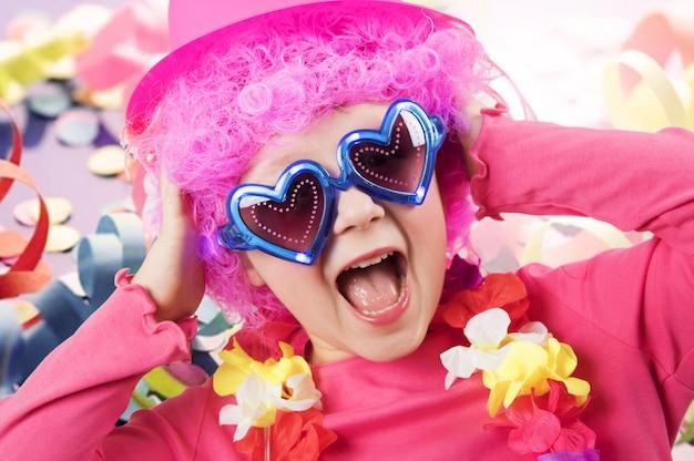 Улыбающаяся маленькая девочка в парике клоуна на белом фоне