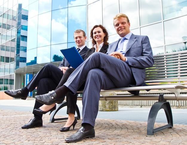 Группа деловых людей, работающих на скамейке