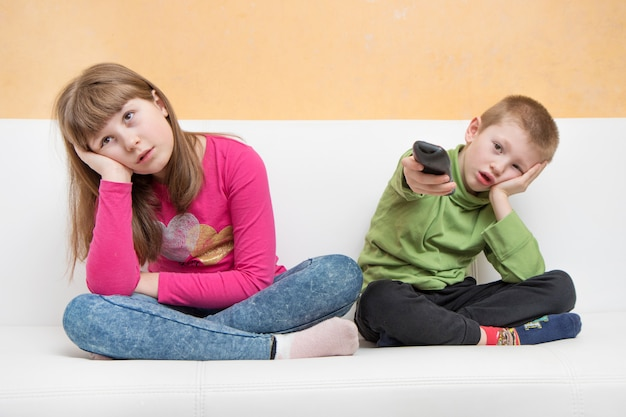 Скучающие дети, сидящие на диване, смотрят телевизор во время карантина коронавируса