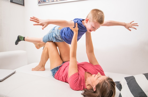 Игривая молодая мать, лежа на диване в гостиной играть, чтобы подражать план с маленьким сыном