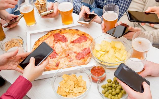 Группа друзей ест пиццу, пьет пиво и использует смартфон в пабе