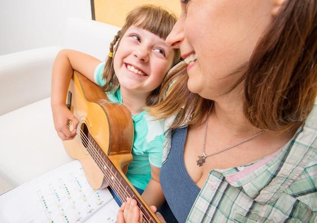 Девочка учится играть на гитаре при поддержке мамы дома