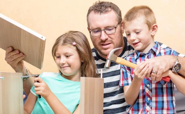 父と子供たちは家具を作っています