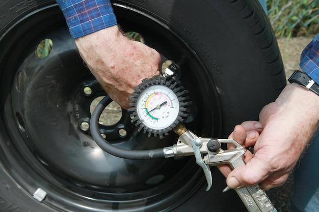 Человек измеряет давление в шинах