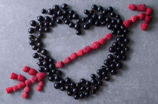 ハート形と新鮮なラズベリーと黒スグリで作られた矢印。トップビューグレーのテーブル