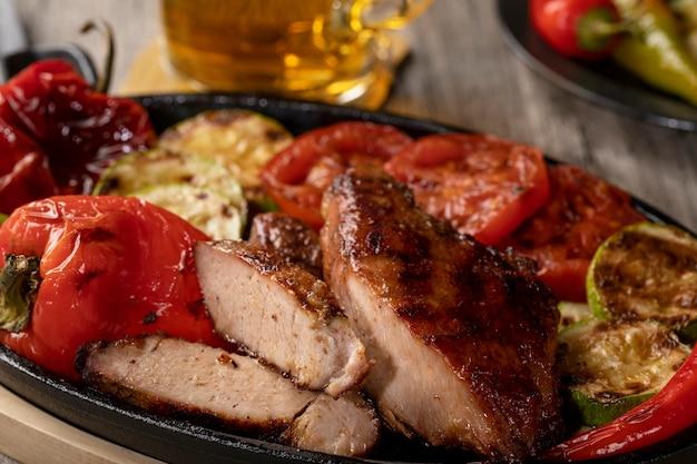 Закройте вверх зажаренного мяса на лотке чугуна с зажаренными овощами на деревенском деревянном столе.