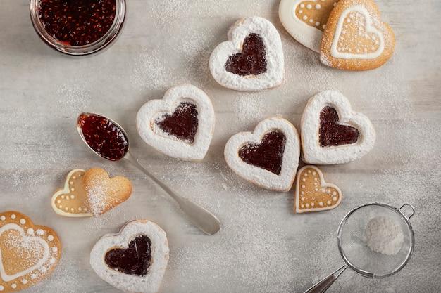 クリスマスやバレンタインの日に白い木製テーブルに自家製のハート型のラズベリージャムクッキー。