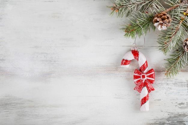 木製のクリスマス組成は白い雪で覆われています。クリスマスキャンデー杖と新年の休日の装飾。コピースペース