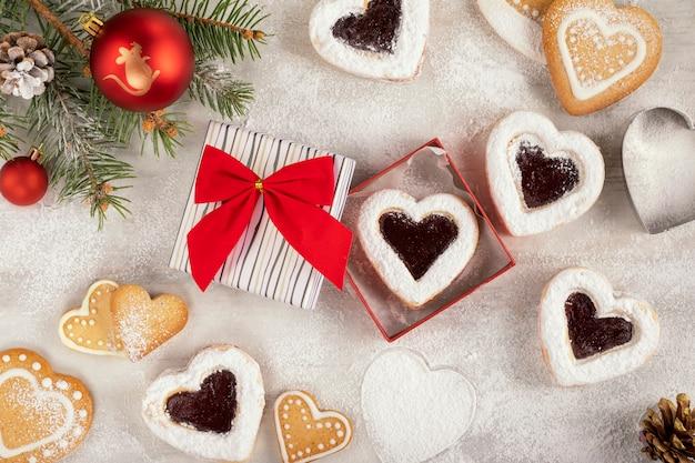 クリスマスやバレンタインの日に白い木製のテーブルに自家製のハート型のクッキーとラズベリージャム。