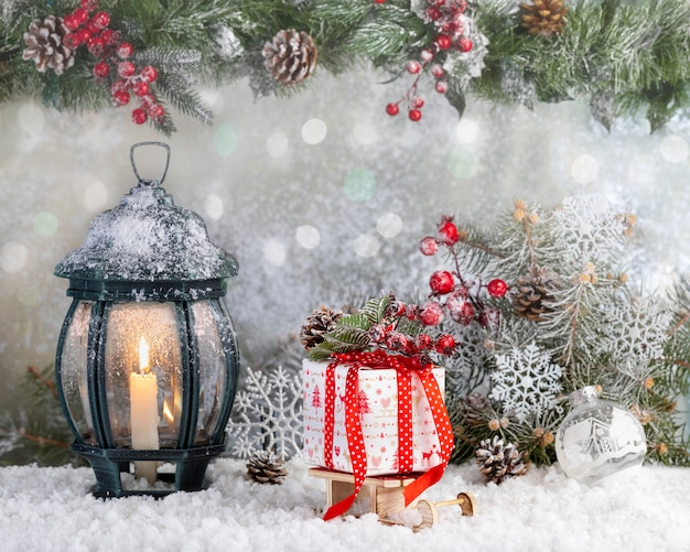 Рождественский фонарь и подарочная коробка на снегу с еловыми ветками