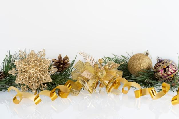 クリスマス装飾金つまらないもの、スノーフレーク、鐘、白の松の枝とコーンの組成