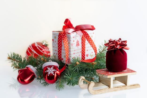 クリスマスの装飾、つまらないもの、ギフトボックス、ガントレット、白のサンタクロースのそりと組成