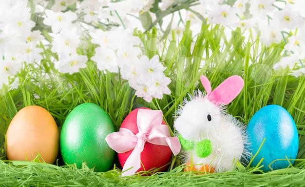 Разноцветные пасхальные яйца и маленький игрушечный зайчик на зеленой траве
