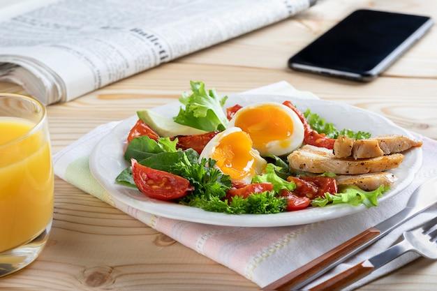 ゆで卵、野菜、ハーブを使ったヨーロッパまたはアメリカンスタイルの健康的なビジネス朝食。閉じる