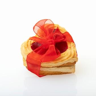 Печенья сформированные сердцем связанные при красный смычок изолированный на белой предпосылке. день святого валентина или день рождения концепции.