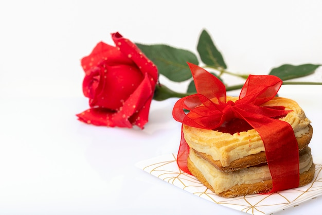 Печенья сформированные сердцем связанные с красным смычком и красная роза изолированные на белой предпосылке. день святого валентина или день рождения концепции.
