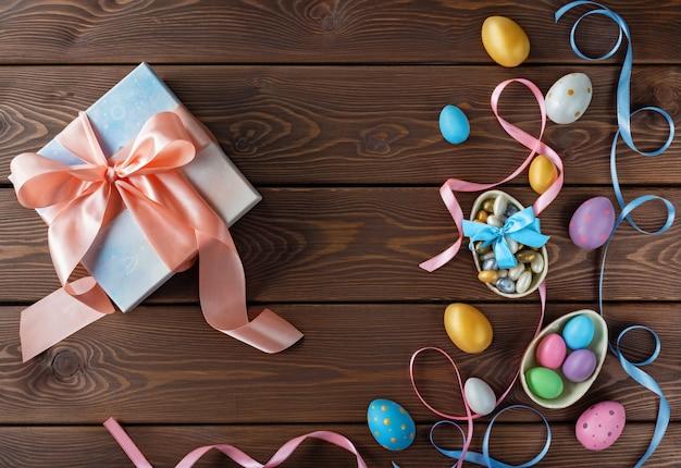 幸せなイースターカード。イースターエッグとギフトボックス。チョコレートと色のリボンの弓で着色イースターエッグ