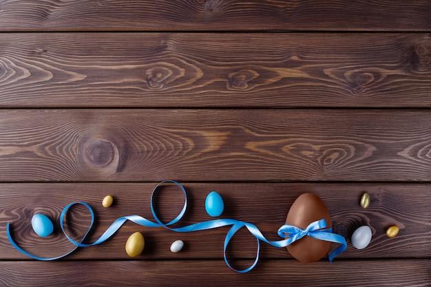 木製の背景に色リボン弓とチョコレートと着色イースターエッグ。幸せなイースターカード。