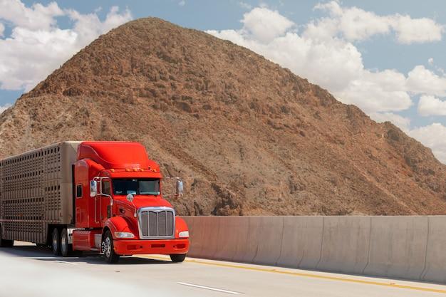 山を背景に高速道路で動物を輸送するためのトレーラーが付いているトラック。貨物のコンセプト。