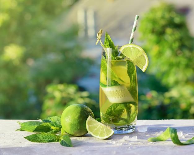 Лимонад или мохито коктейль с лаймом, огурцом и мятой, холодный освежающий напиток или напиток со льдом, на открытом воздухе. холодная детокс-вода с лимонной и бумажной соломкой. летний напиток с копией пространства.