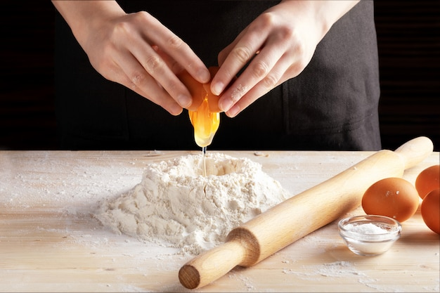Вид спереди женских рук, делая рецепт с деревянной скалкой