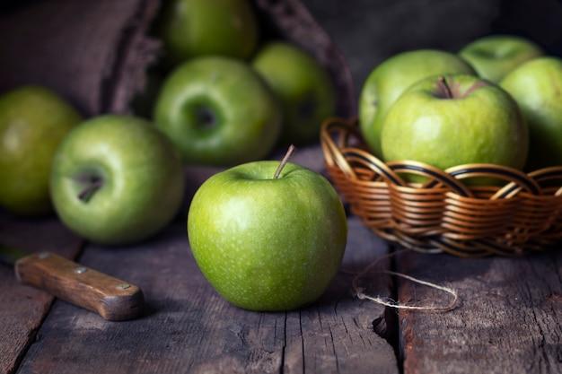 Зрелые зеленые яблоки на старой деревянной предпосылке.