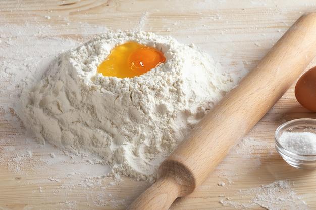 Разбитое сырое яйцо в муке и скалке