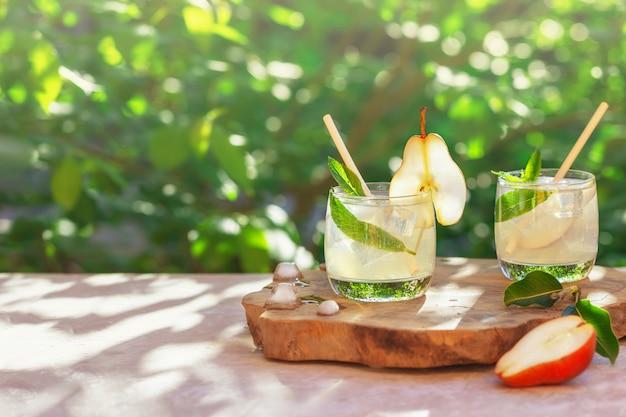 Два бокала летнего освежающего прохладного напитка или коктейля из груш и мяты