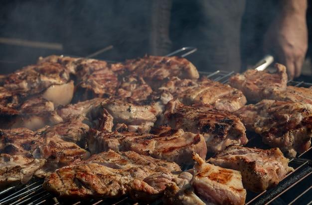 Мясо на гриле. стейки из говядины или свинины на гриле с дымом. барбекю на природе.