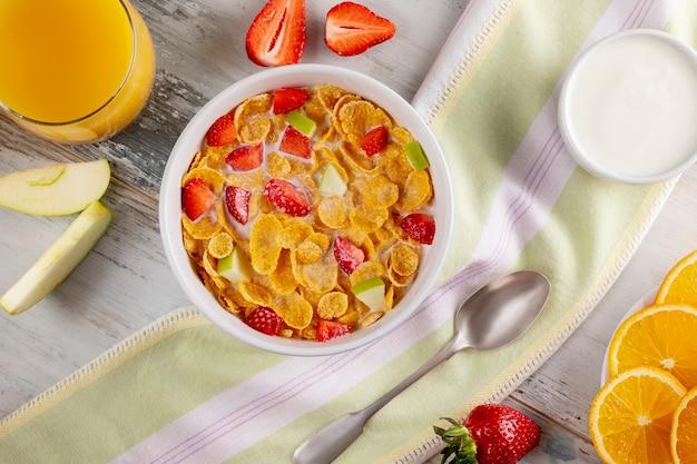 健康的な朝食コーンフレークとイチゴ、ミルク、ヨーグルト、オレンジジュース。バイオ健康。閉じる