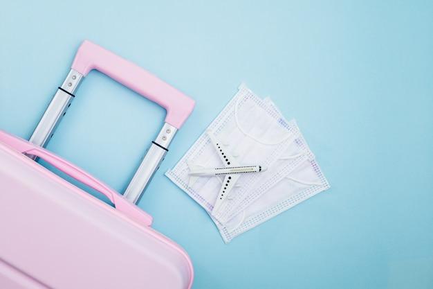 青の白い飛行機モデルと衛生フェイスマスクとピンクの荷物