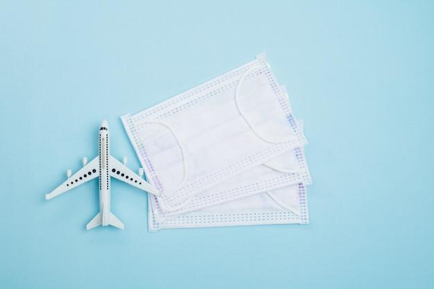 旅行とヘルスケアの概念のための青の衛生フェイスマスクと白い飛行機モデル