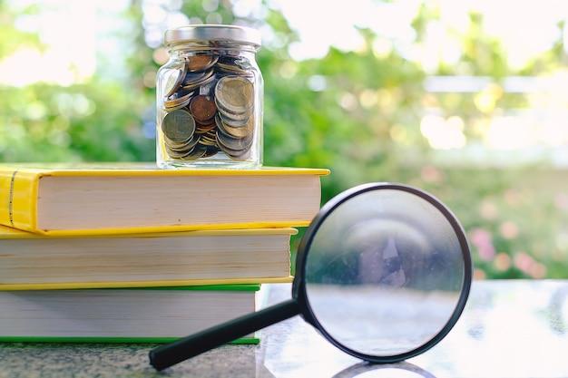Денежные монеты в стеклянной банке на книгах и увеличительном стекле