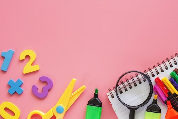Школьные принадлежности на розовом фоне для образования и концепции школы
