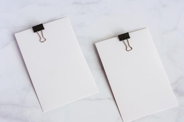 白い大理石の背景にバインダークリップと白い紙のカード
