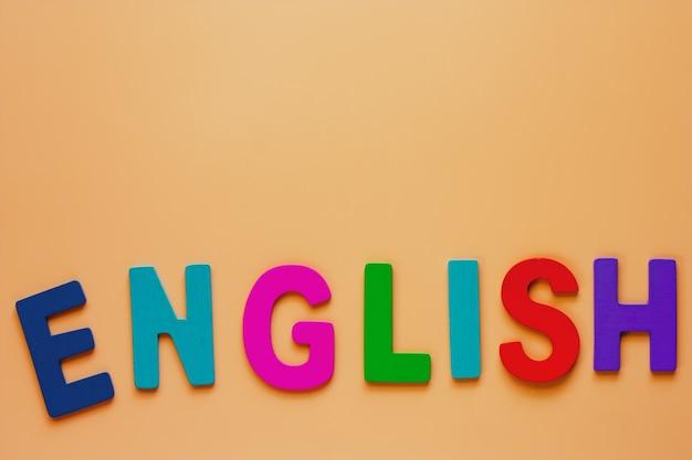 概念を学習するためのベージュ色の背景に木製の文字から英語の単語