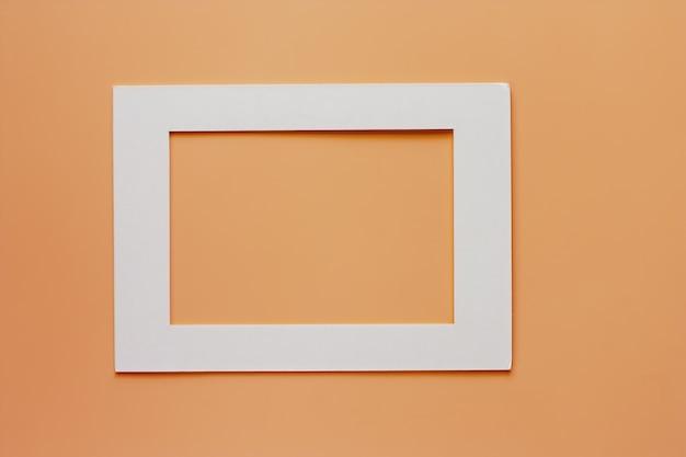 ベージュ色の背景に白い紙のフレーム