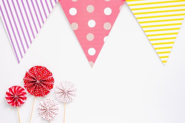 パーティーの装飾のための白い背景に赤と白の紙のファンとカラフルな紙の旗