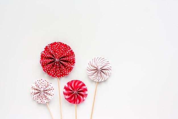 パーティー装飾のための白い背景に木製の棒と赤と白の紙のファン
